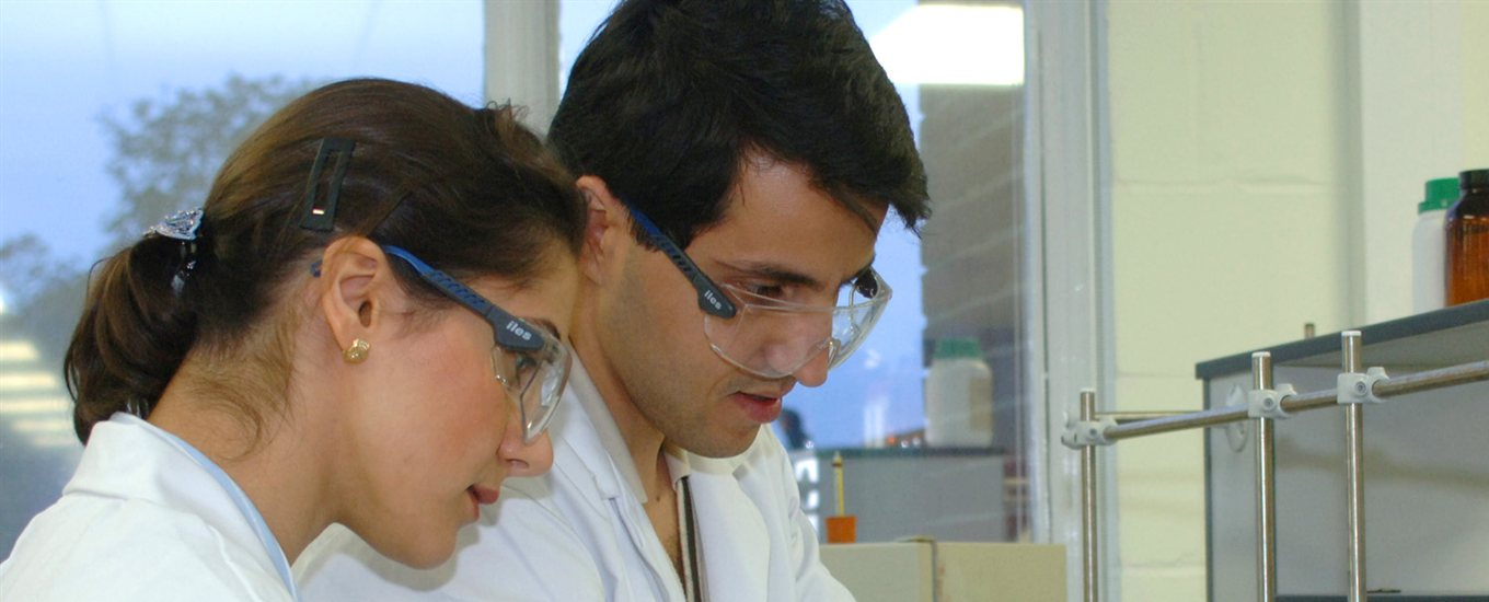 2 students in white labcoats and blue goggles working together