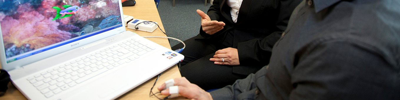 2 people sitting at a laptop with a fish on the screen, one has wires taped to their fingers to monitor for Epilepsy
