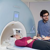 A student talks to a woman in the MRI scanner