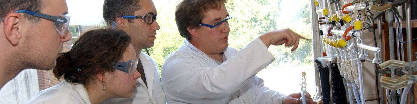 4 students in white lab coats and blue goggles watching a demonstration