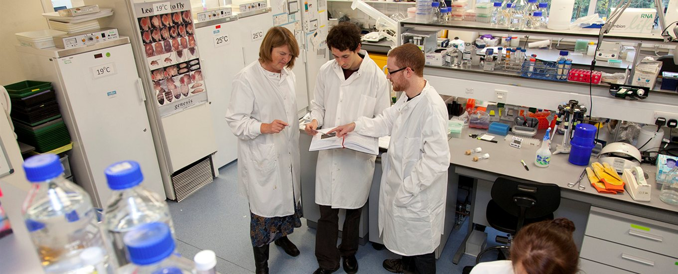 Sarah Newbury and researchers in white lab coats, standing in a lab and consulting a text book together