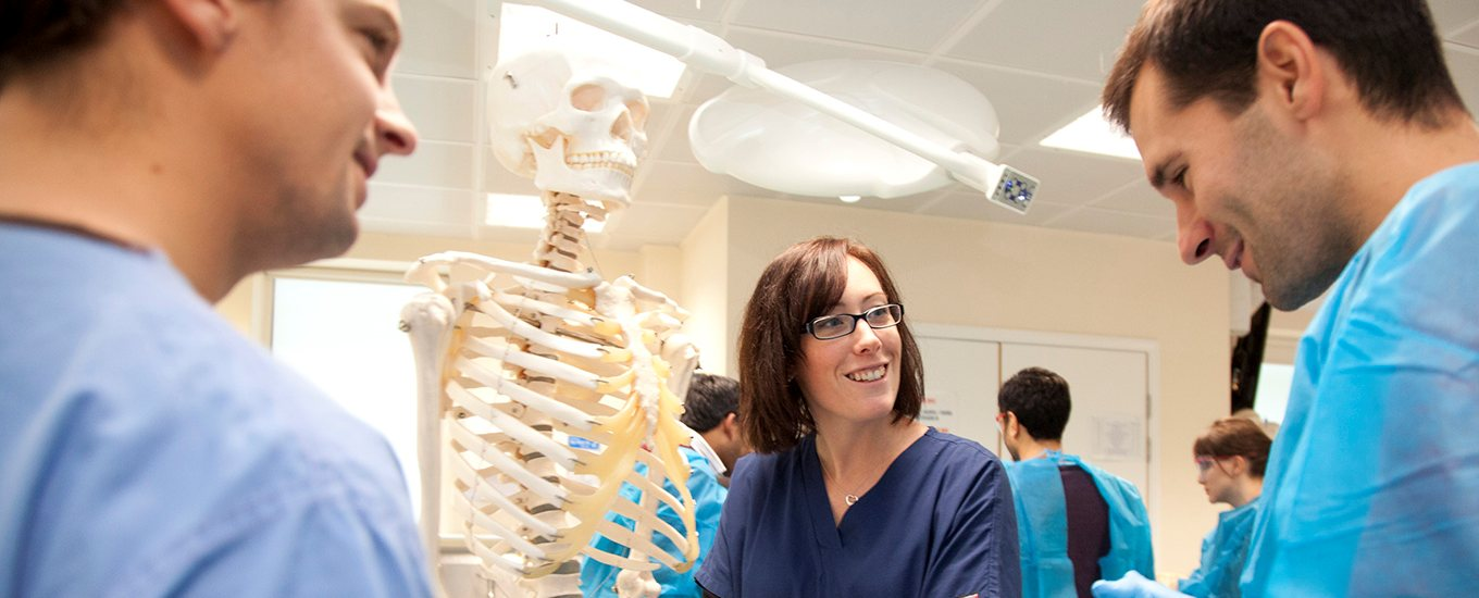 Prof Claire Smith and students and skeleton model in dissection room