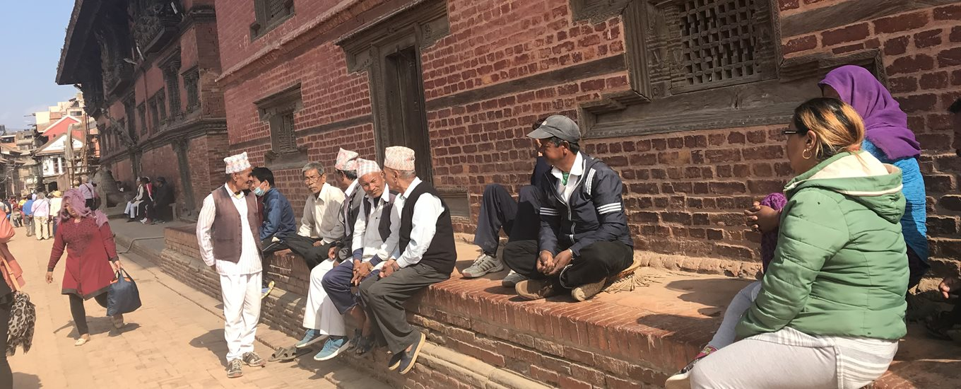 People sitting on steps outside a building in Nepal