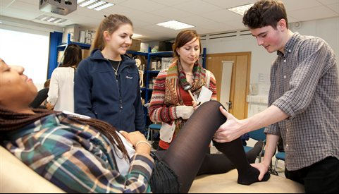 Students testing reflexes leg