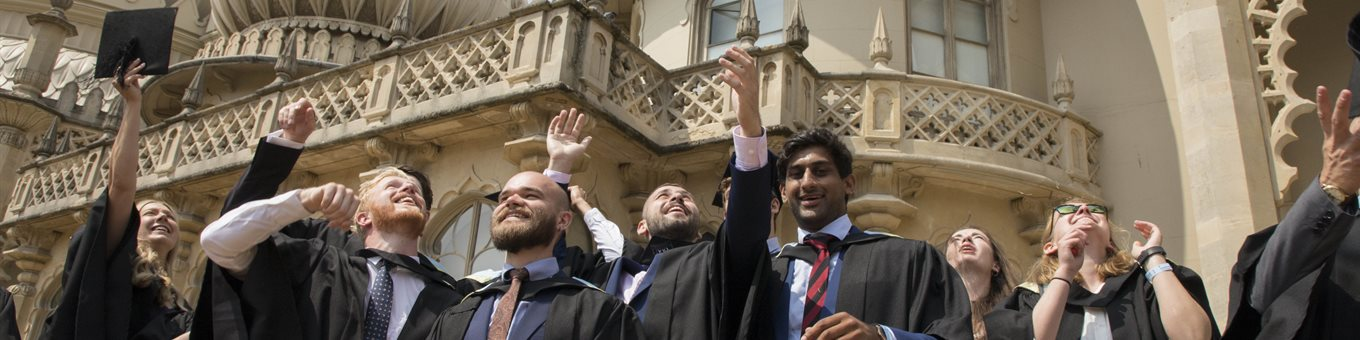 Graduands throw their mortar boards in the air outside Brighton Pavilion