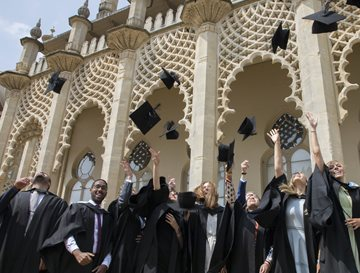 Graduating students in front of Brighton Dome, throwing mortar boards in the air