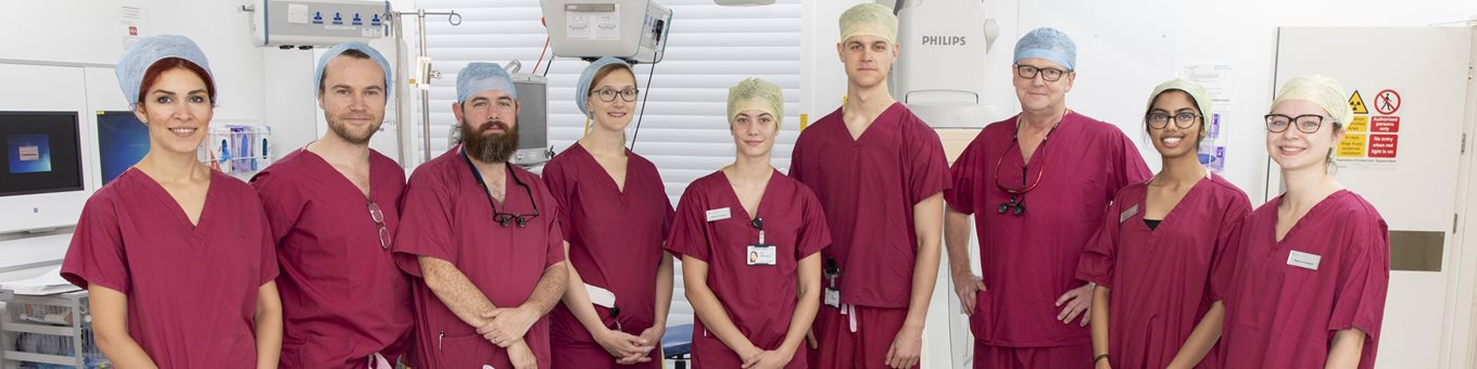 Student doctors and hospital staff in scrubs in operating theatre