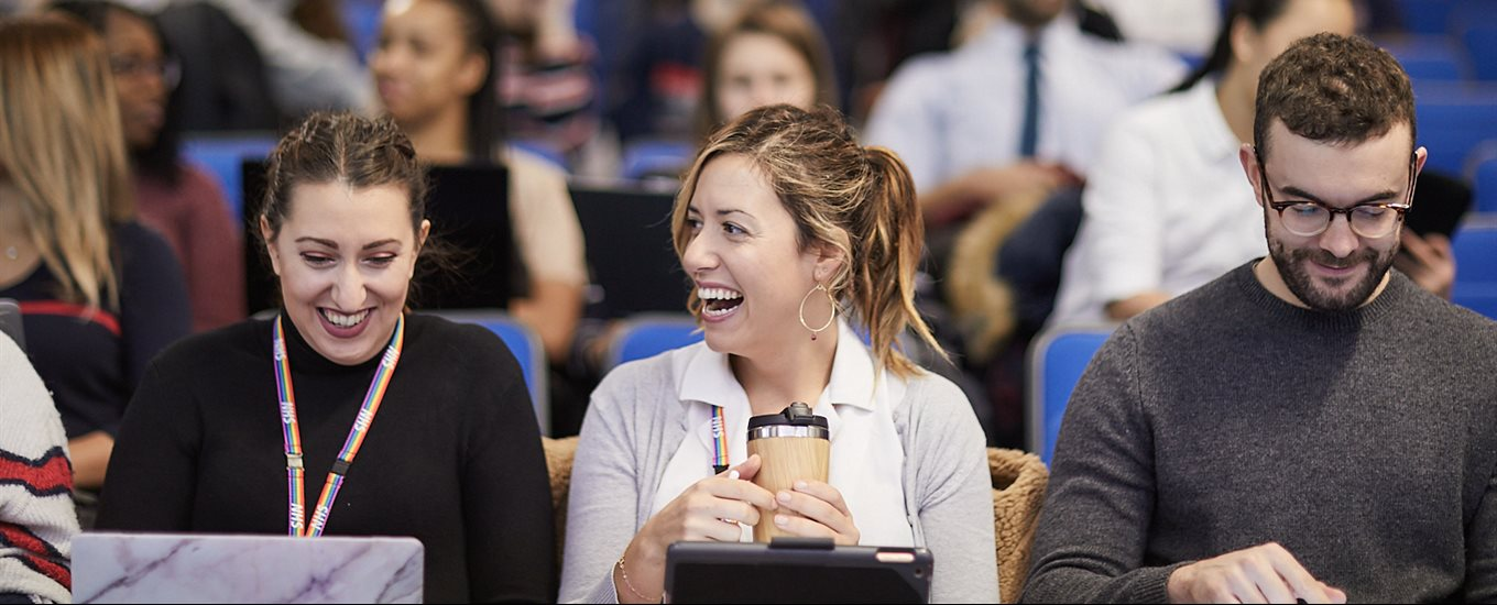 Two smiling female students in a lecture